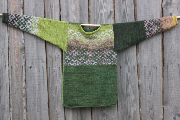 Oak Green Latvian symbols reversible unisex sweater knit by Wrapture by Inese and hung flat on side of woodshed size M