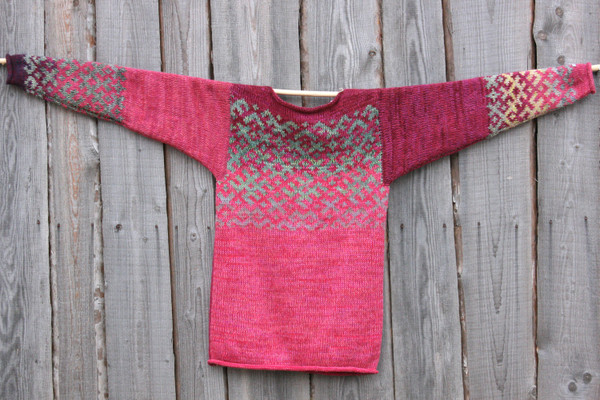 Roses inspired Latvian symbols reversible unisex sweater knit by Wrapture by Inese and hung flat on side of woodshed size M