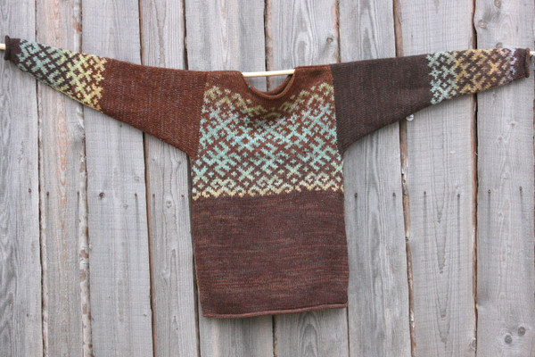Chocolate Brown inspired Latvian symbols reversible unisex sweater knit by Wrapture by Inese and hung flat on side of woodshed size M