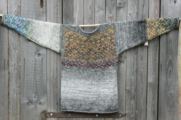 Rocky Beach Latvian symbols sweater flat on side of woodshed size L