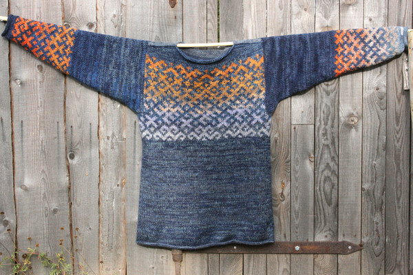 Denim Sunset Latvian symbols in size XL hung flat on a wooden wall. Knit by Inese for Wrapture by Inese, unique and one of a kind.