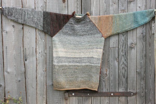 Rock Face reversible raglan pullover where the sweater is hung on a wood shed, designed and knit by Wrapture by Inese
