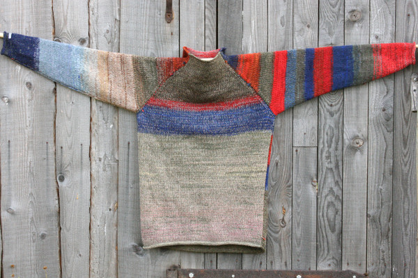 Maasai reversible raglan pullover where the sweater is hung on a wood shed, designed and knit by Wrapture by Inese