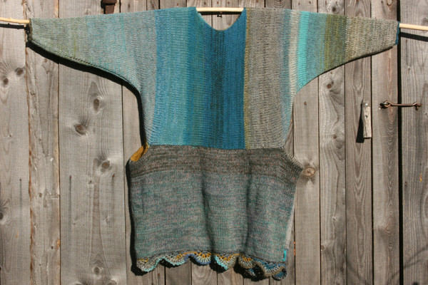 Fjord Edge inspired scalloped hem sweater reversible dress hung on wood pole on side of woodshed, knit side out, knit by Wrapture by Inese