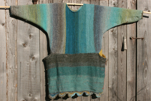 Fjord Edge inspired scalloped hem sweater reversible dress hung on wood pole on side of woodshed, purl side out, knit by Wrapture by Inese