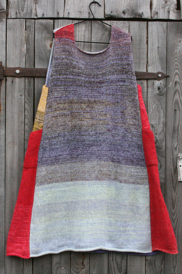 Tatarian dogwood colors inspired trapeze dress hanging on a coathanger against a wooden wall Wrapture by Inese