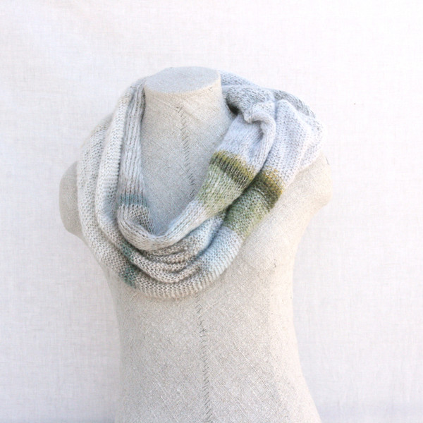 Snow kid mohair and silk one of a kind loop scarf on dress form with white background. Knit by Inese in white, silver sparkle, green, grey