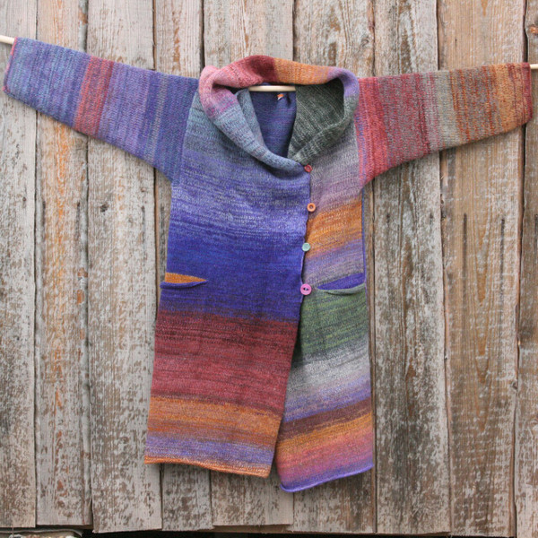 Plum color card inspired felted wool coat knit by Wrapture by Inese hung on side of woodshed