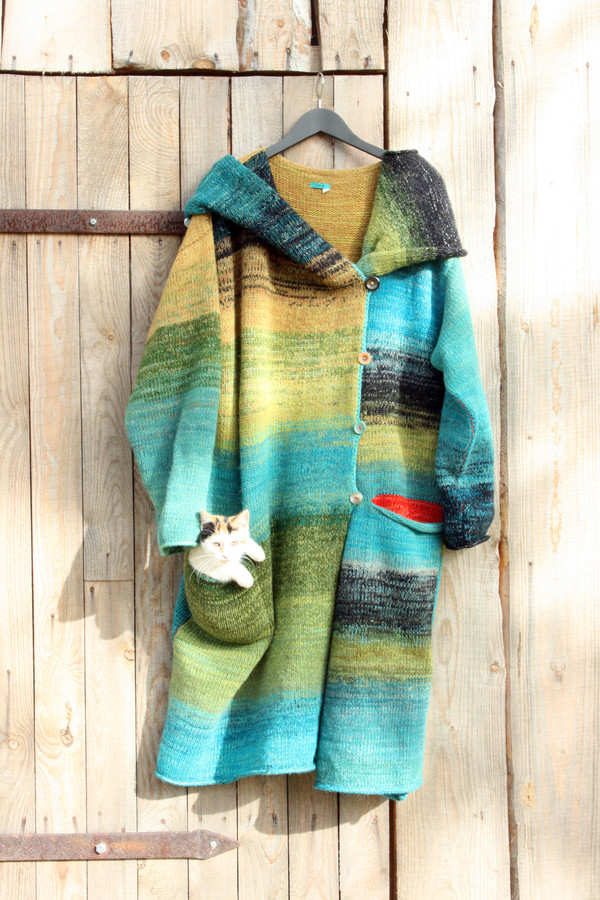 Cat in pocket view of turquoise and green one of a kind felted wool coat on hanger on woodshed door. Knit and designed by Wrapture by Inese