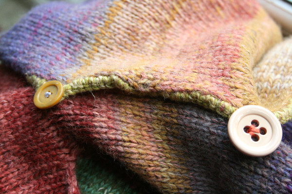 Closeup of Bitene M felted wool coat unmatched button detail with crochet edge and button loops. Knit by Wrapture by Inese