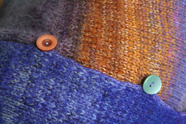 Closeup of Plum S felted wool coat unmatched button detail with crochet edge and button loops. Knit by Wrapture by Inese