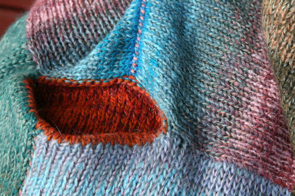 pocket detail in closeup of unique ombre knitting with contrast stitching in scalloped hem sweater dress knit by Wrapture by Inese inspired by Barcelona Door color story