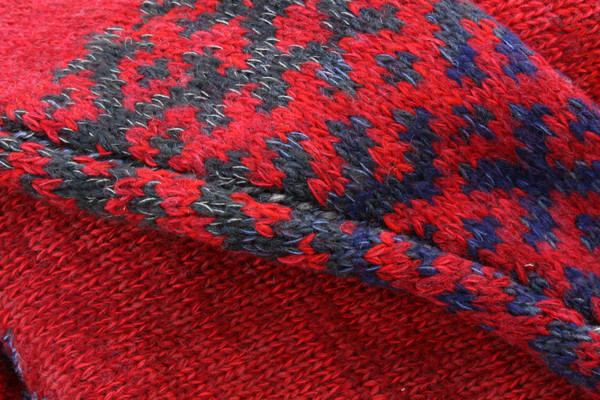 closeup of fire red grey Latvian symbols sweater showing pattern detail designed and knit by Inese for Wrapture