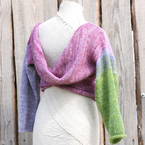 Lilac Buds lavender green x-tee on dress form showing crossover worn in back in front of wood wall knit and designed by Inese for Wrapture