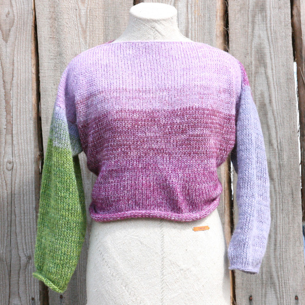 Lilac Buds lavender green x-tee on dress form showing front view if  crossover is worn in back in front of wood wall knit and designed by Inese for Wrapture