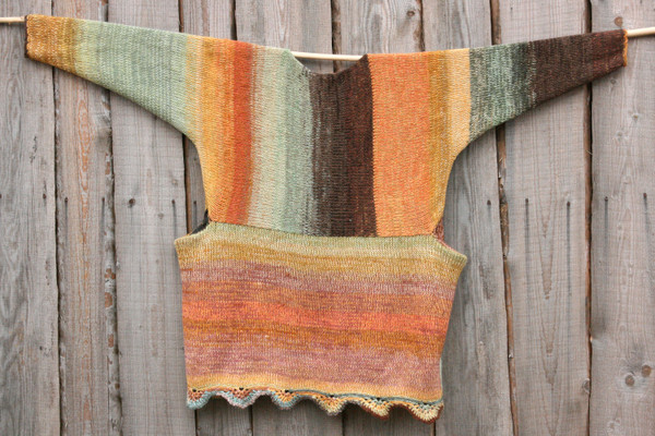 Ancient Woods inspired scalloped hem sweater reversible dress hung on wood pole on side of woodshed, purl side out, knit by Wrapture by Inese