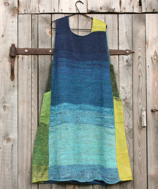 Mirror Lake trapeze dress on coathanger hung on woodshed door knit by Inese iris Liepina of Wrapture by Inese