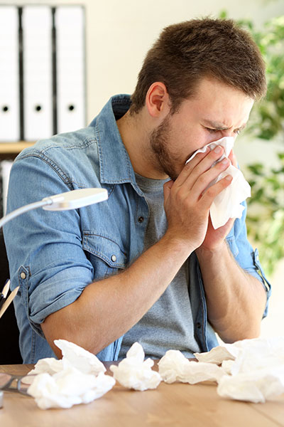 Man sneezing and suffering from allergies