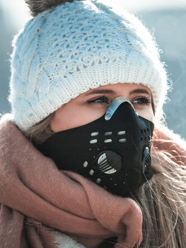 Woman wearing a sport PM2.5 respirator on busy city streets