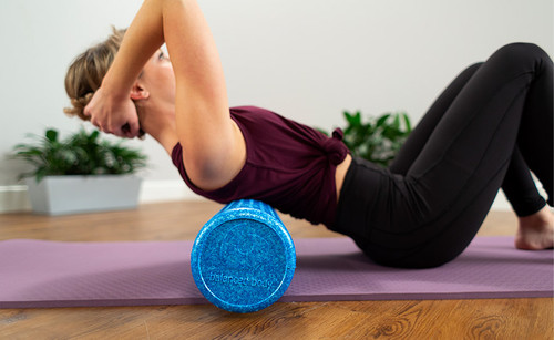 pilates instructor training with blue foam roller