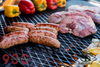 Argentinian BBQ grill cooking meat and sausages over a open wood fired pit.