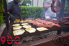 Eggplant and asado meat being cooked on Argentine grill.