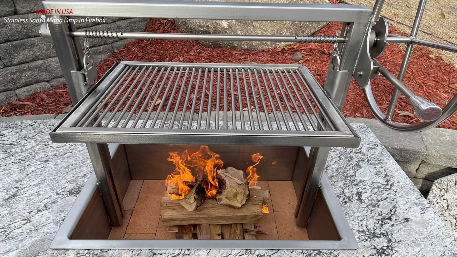 Stainless Santa Maria Drop In firebox with height adjustable grill grate installed in outdoor kitchen island