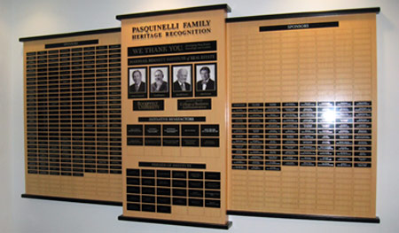 Three-panel bamboo laminated donor wall, with black metal dimensional lettering, metal printed photos and black aluminum plates to recognize donors and sponsors.