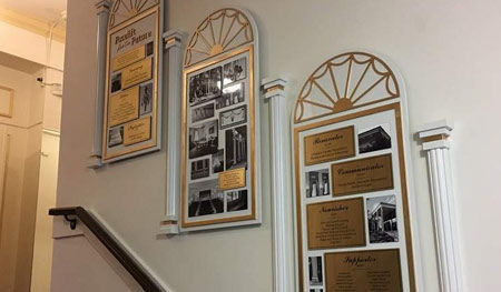 White, laminated wood arch plaques with matching wood columns mimic the iconic building exterior. Donors recognized on imprinted brass plates. Photos of renovaton are printed on collage of metal plates.