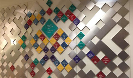 Assembled on large acrylic panels for easy hanging and removal, this wall incorporates satin aluminum blocks and colorful acrylic to form a quilt pattern with each color representing a level of giving.