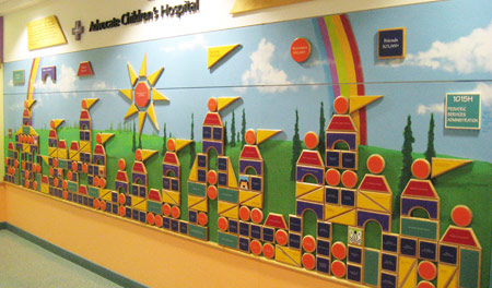 Wood shapes that mimic a child's building blocks, form a castle over a hand-painted mural.  Each piece has a colored personalized donor nameplate, representing a specific level of giving.