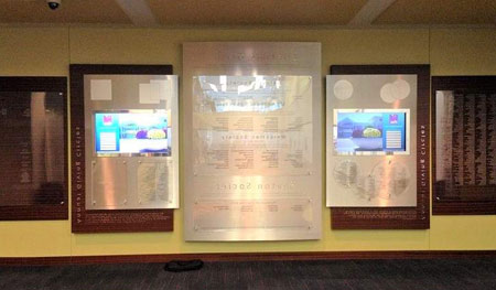 Dark cherry wood boards surround a silver, metal laminated center board. Donor names are printed on Lexan, sandwiched between acrylic panels. Wall includes dimensional lettering and two digital, touch-screen displays.