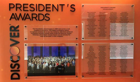Floor to ceiling orange graphic, separates hall section from others. Top panel etched and color-filled in black. Remaining panels double glass plates, with awardee names printed on Lexan. Copy and logo are 1/2in. black acrylic.