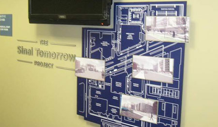 Wall is installed in a doctor's lounge and showcases a map of new hospital location and additions. Renderings are printed on metal and layered at the top. Digital display loops with donor information and project updates.