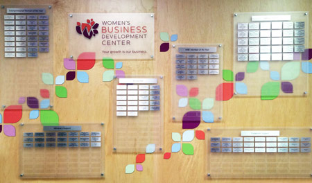 A combination of frosted acrylic panels and standoffs, decorated with silver, engraved donor nameplates and colorful laser-cut acrylic leaf figures for contrast and dimension.