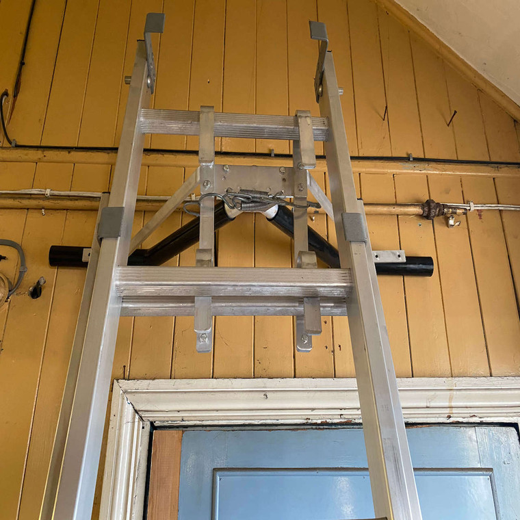 Industrial ladder Stand Off against wall indoors
