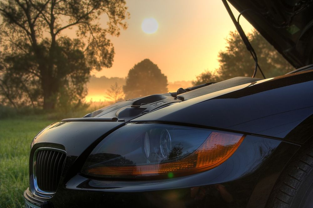 A car with an extended strut in front of a sunrise