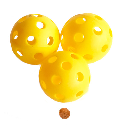 Yellow plastic tossing balls with holes - softball