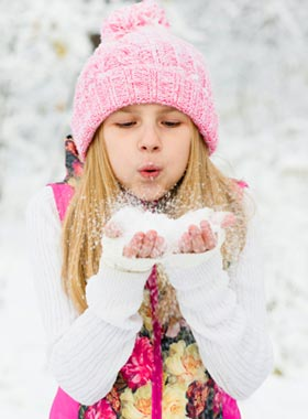 Girl blowing snowflakes at winter carnival