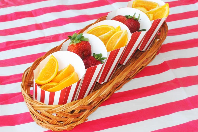 Healthy Carnival Food Ideas - image shows strawberries and oranges in a basket on red and white tablecloth