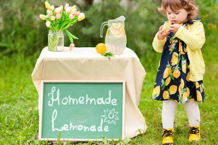 Cute toddler next to a lemonade stand outdoors for a carnival blog