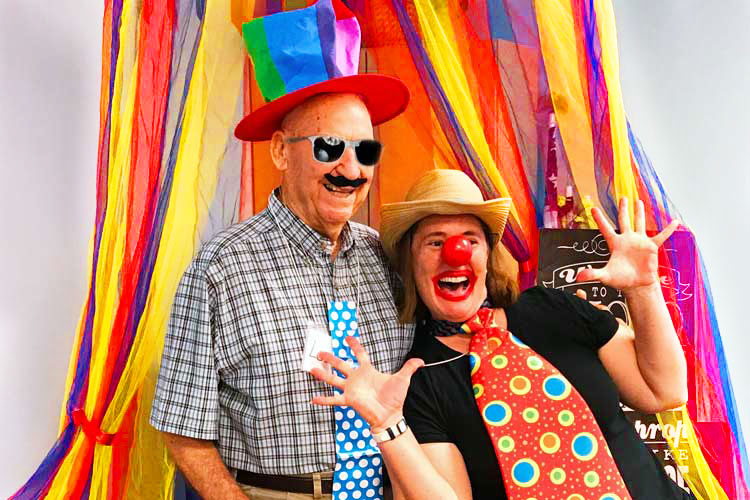 Elderly man at carnival with happy clown
