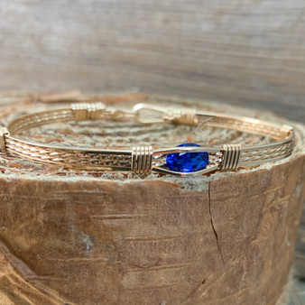 """This bracelet features a synthetic sapphire gemstone in a Classic all yellow gold band in a standard size 7""""."""