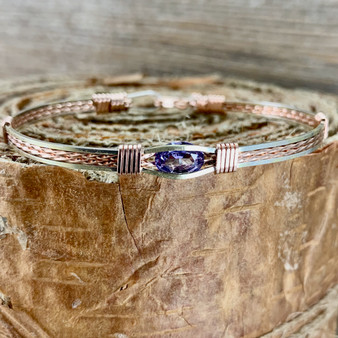 This IN STOCK synthetic Alexandrite is a great choice. If you want to decide the metal type, the band design and the size that fits you, please refer to the CUSTOM tab to place your order.  Shown in a silver and rose gold combination in a classic design, this retails for $129.