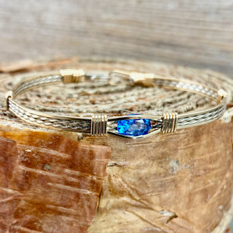 IN STOCK is a Yellow Gold and Argentium Sterling Silver bracelet paired up with yellow gold wraps. This striking Kashmir Blue Topaz makes a wonderful addition to anyones jewelry accessories.