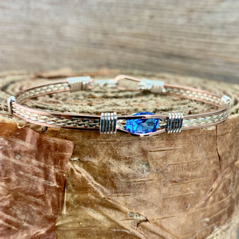 IN STOCK is a Yellow Gold and Argentium Sterling Silver bracelet paired up with silver wrap wires. This striking Kashmir Blue Topaz makes a wonderful addition to anyones jewelry accessories.