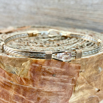 Rutilated Quartz is considered a semi-precious gemstone,  versitile and rich is a good way to describe this gemstone. This is one of those bracelets that goes with everything with this two tone bracelet band.