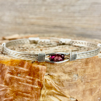 Shown is an all Argentium Sterling Silver Classic Bracelet featuring a Rhodolite Garnet. This garnet is so functional and gorgeous at the same time with a soft burgundy pink hue. Sometimes called an Orissa Garnet it is sure to be a treasured treat for years to come.