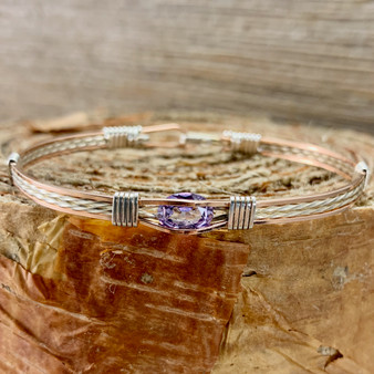The June Birthstone is a Synthetic Alexandrite offered with a rose gold and Argentium Sterling silver band. This soft combination of metals paired up with this gemstone is a true winner. Many of our customers comment about the durability and versatility of these beauties!
