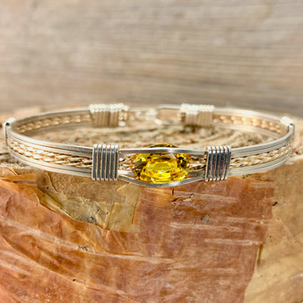 Shown is a Synthetic Golden Topaz wire wrap bracelet paired up with an Argentium Silver and Yellow Gold classic bracelet band. We handcraft each one to suit your needs. We have been in business since 1993, handcrafting jewelry that is beyond ordinary.